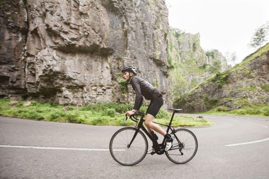 Cycliste avec vélo de route en montée