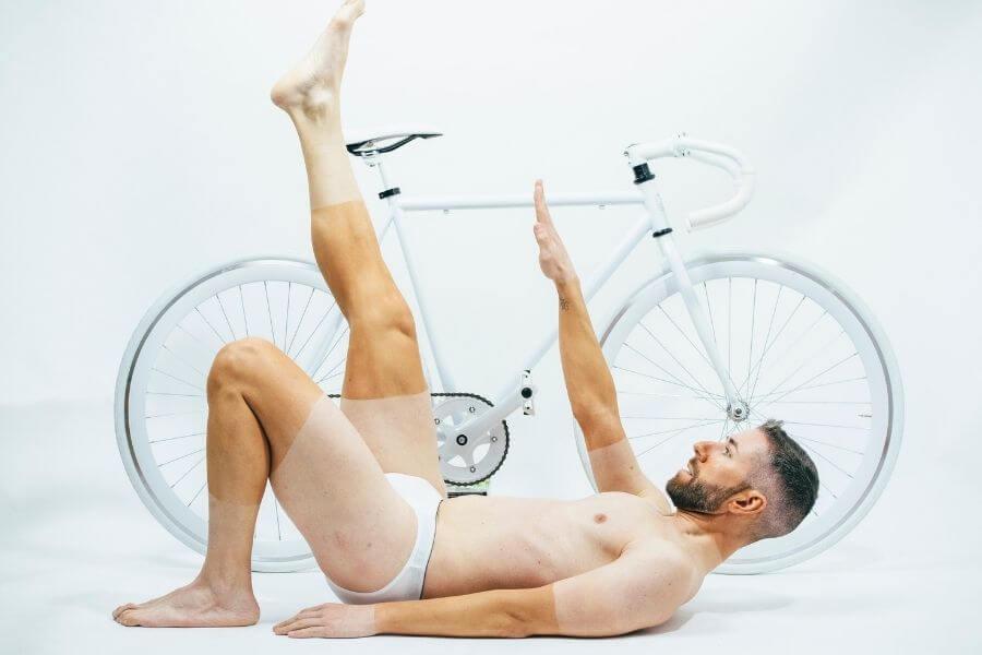 Cycliste allongé nu avec bronzage partiel