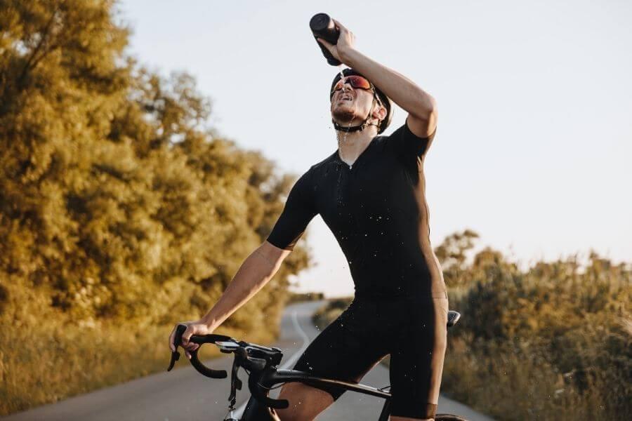 Cycliste déshydraté avec vélo de route et lunettes en été