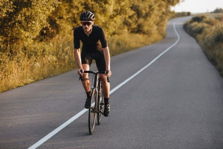 Cycliste avec vélo de route et lunettes en été